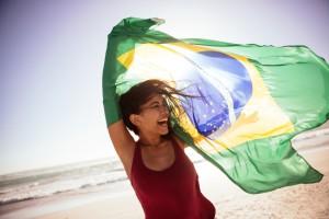 Frau hält eine brasilianische Flagge am Strand